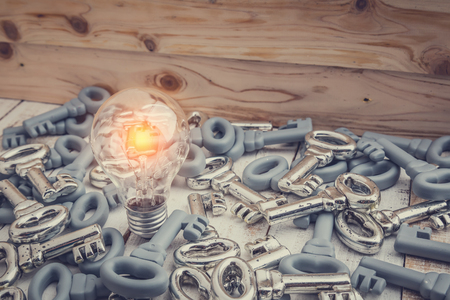 hustle: glow light bulb with heaps of keys on wooden floor business ideas concept Stock Photo