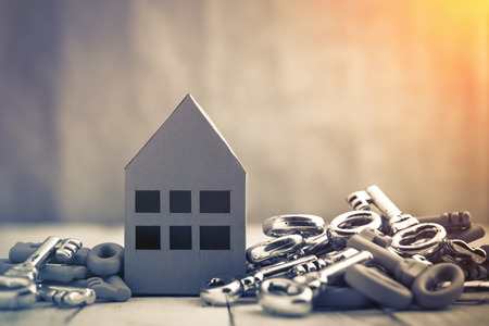 Concept image for new home with shiny house keys on a white wooden background. Copy space.house business concept