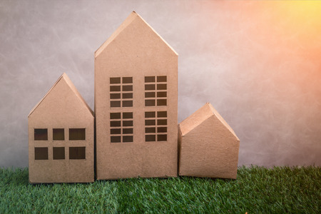 building loan: model of cardboard house on green grass floor and grey background. house building, loan, real estate or buying a new home concept.