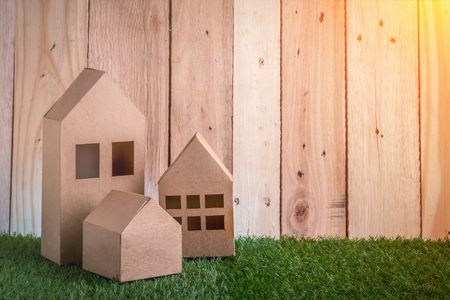 building loan: model of cardboard house on green grass floor and wooden background. house building, loan, real estate or buying a new home concept.