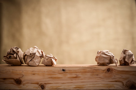 sheet of paper with word ideas concept and crumpled paper balls on table business ideas concept