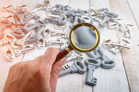 Concept image of a keys home inspection. A male hand holds a magnifying glass over a key of miniature house.