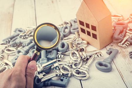 home inspection: Concept image of a home inspection. A male hand holds a magnifying glass over a miniature house.