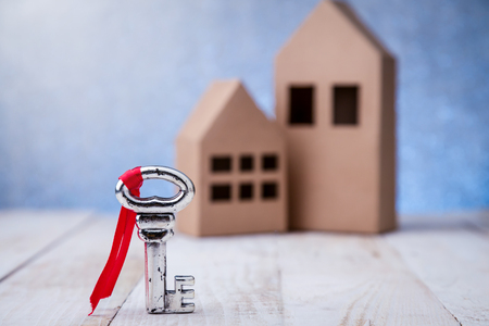 building loan: model of cardboard house with key against bokeh background. house building, loan, real estate or buying a new home concept. Stock Photo