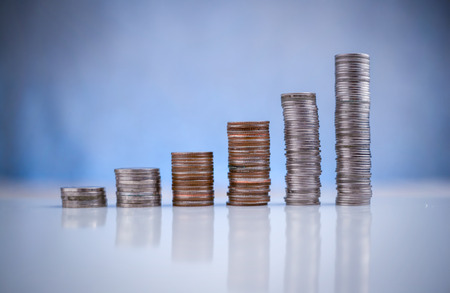 stack of coins on white floor againt with blur bokeh background business concept