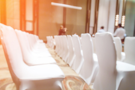 seating area: Blurred background of empty chairs with people in convention or meeting room Stock Photo