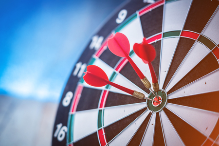hitting: Red dart arrow hitting in the target center of dartboard Stock Photo