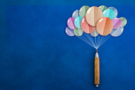 uplift: wooden pencil with balloons shape paper cut on blue leather background creativity ideas concept