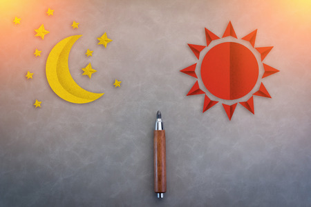 wooden pencil: wooden pencil with sun and moon paper shape season concept on grey background