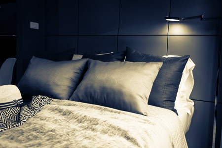 flair: Bed maid-up with clean white pillows and bed sheets in beauty room. Close-up. Lens flair in sunlight. Stock Photo