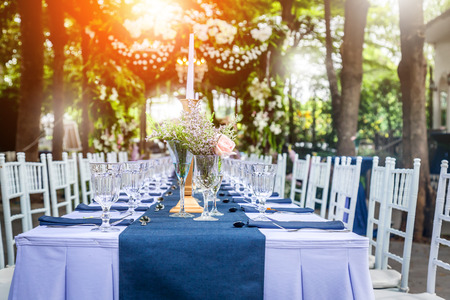 glass of vase with beautiful flowers with dining set  at a Wedding Reception with light flare effect Stock Photo - 64981741