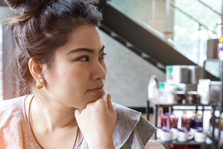 skepticism: Thinking business woman with free copy space in cafe background with finger at face, asian beauty