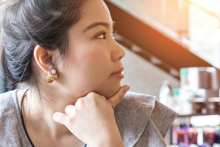 Thinking business woman with free copy space in cafe background with finger at face, asian beauty