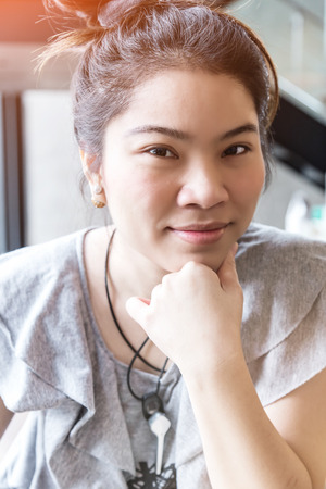 free thinking: Thinking business woman with free copy space in cafe background with finger at face, asian beauty