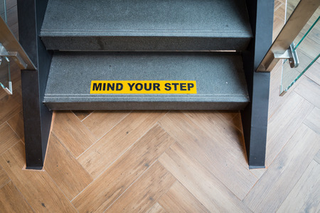 stating: Yellow and black warning sign on stairs stating Watch your Step signifying a potential trip hazard, steep stairs and care to be taken when going up or down stairs