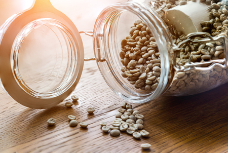 flavored: roasted coffee beans,Coffee beans in glass jar on wooden background. Stock Photo