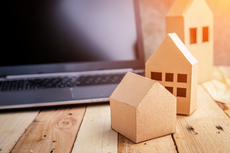 housing project: house concept with cardboard model next to black screen notebook with free copyspace Stock Photo