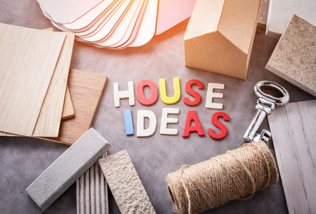 architectural studies: home ideas concept with mockup paper house model with material sample and wooden text with silver key Stock Photo
