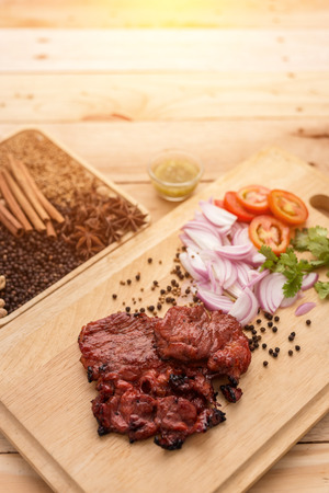 cut through: Delicious grilled marinated rack of lamb cut through to show the texture on a wooden chopping board with fresh ingredients and vegetables