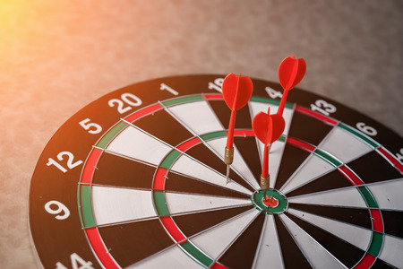 Right on target concept using dart in the bullseye on dartboard business success concept