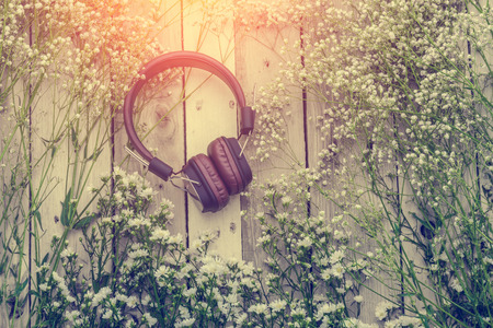 music therapy: headphone with frame of beautiful flower on wooden background music therapy concept Stock Photo