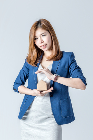 show window: beautiful asian businesswomanwith house paper model with free copyspace for your text house concept