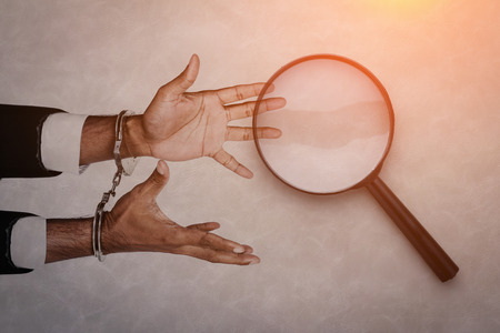 constraint: business man try to reach magnifying glass to free from handcuff business problem concept with free copyspace