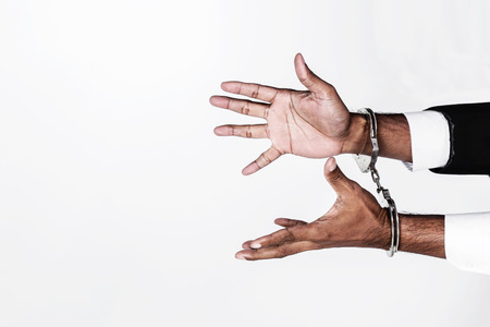 Businessman hands fettered with handcuffs isolated on white with high contrast image tone and free copyspace for your text Stock Photo
