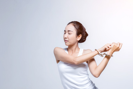 pretty asian girl with handcuff and trying to escape people concept on white background