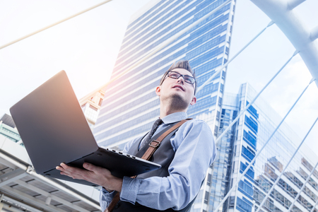 Young handsome businessman standing with laptop in the big city and purposefully looking away in downtown city sathorn thailand Stock Photo