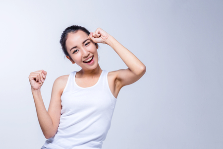 Beautiful brunette Asian girl in white tshirt stretching, relaxing on white background Archivio Fotografico