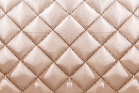 White beige velvet capitone textile background, retro Chesterfield style checkered soft tufted fabric furniture diamond pattern decoration with buttons, close up