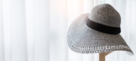 brim: Womens Wide Brim Straw Hat hand on wood stand with light from white window curtain in daytime