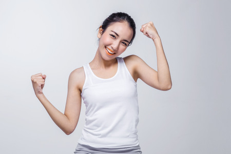 Belle fille asiatique brune en tshirt blanc qui s'étend, se détendre sur fond blanc Banque d'images
