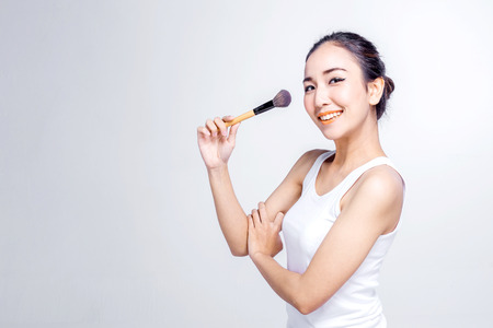 Beauty makeup asian woman smiling closeup. Beautiful young woman applying foundation powder or blush with makeup brush. Isolated on white background.
