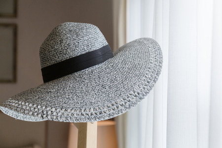 Womens Wide Brim Straw Hat hand on wood stand with light from white window curtain in daytime