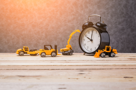 vintage black alarmclock with toy car business construction ideas concept on wooden floorand grey leather background