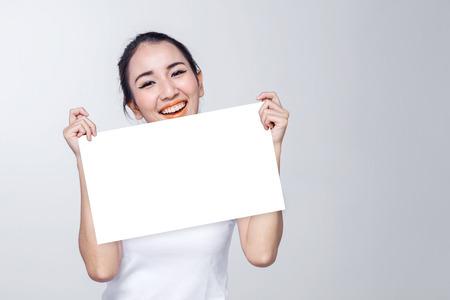 美しい女性の肖像画。白い背景のテキストの無料 copyspace と肌と顔のケア概念持株白い看板 写真素材