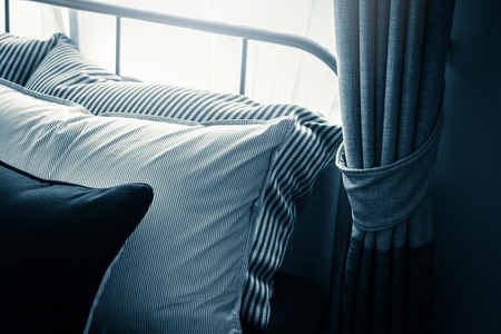 Bed maid-up with clean white pillows and bed sheets in beauty room. Close-up. Lens flair in sunlight. Stock Photo