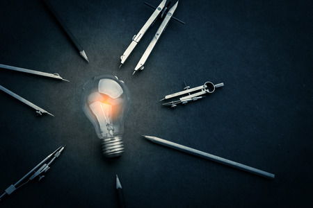 drawing tool with glow light bulb on leather background creativity  ideas concept