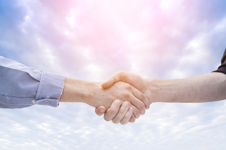 business handshake with Beautiful soft clouds and blue sky background Stock Photo