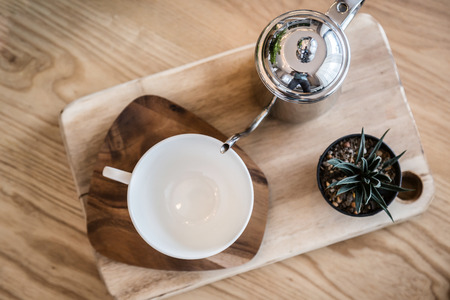 set of tea or coffee with small teapot on wooden table with room interior background  in morning time