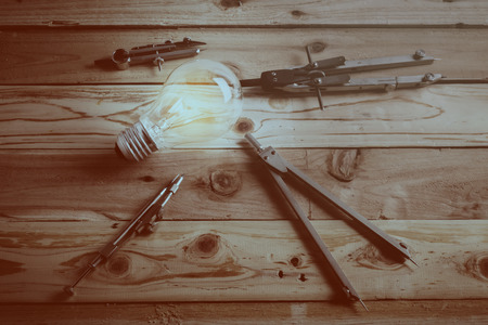 re design: drawing tool with glow light bulb on leather background creativity  ideas concept