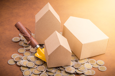 house rental and mortage  business concept with cardboard house model with heap of coin money on leather floor Stock Photo