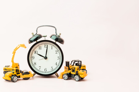 time concept with black alarmclock and consruction toy car with free copyspace for your text