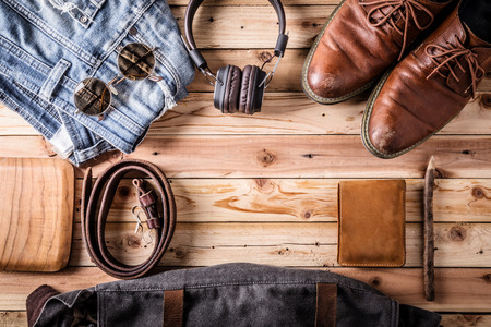 travel stuff concept with jeans leather wear headphone on old vintage wooden floor with free copyspace for your text