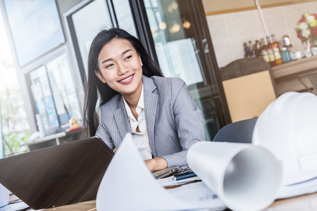 smart asian business woman working on table top with laptop paper coffee smartphone
