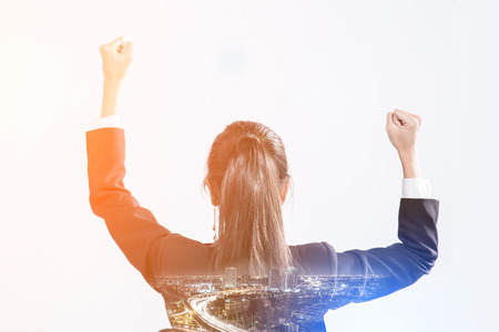 raise your hand: business success concept with business girl raise hand in to the sky with image pf night city double exousure with free copyspace for your text