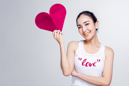 beautiful asian teen with white tshirt and red heart paper shape with love ideas concept on white background