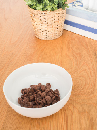 chocolate cereal: Chocolate cereal in white bowl on wood table